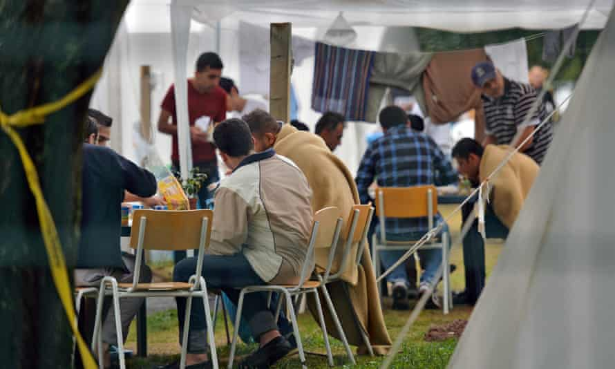 Refugees sit in tents on the compound of a reception centre in Chemnitz, east Germany.