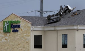 A vehicle rests on top of a three-storey hotel after a tornado touched down in in Floresville, Texas, on Friday.