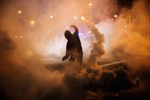 A protester throws a tear gas canister back toward riot police