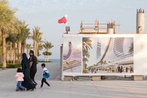 People walk past signs for a luxury hotel under construction in the marina district