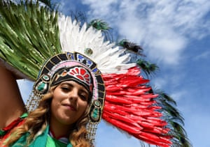 A Mexico fan adornes feathers to cheer on her country