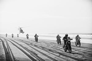 Motorbike competitors traverse Los Palos beach are followed by a TV helicopter