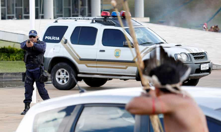 A member of Brazil's riot police trains his gun at Brazilian Indians