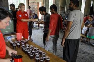 Local Red Cross volunteers offer food and drink to migrants near Croatia's border in Bihać, Bosnia-Herzegovina