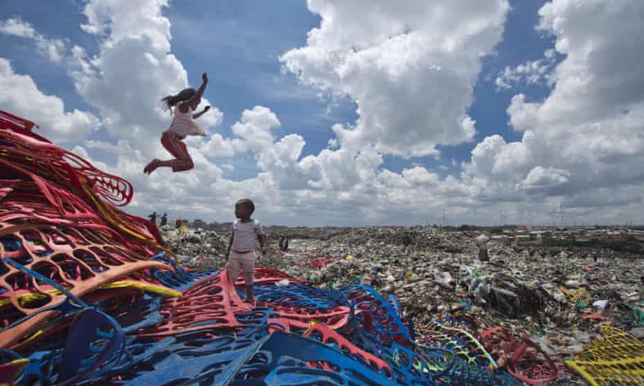 Children play on plastic left over from the manufacture of flip-flops at a dump in the Dandora slum of Nairobi, Kenya.
