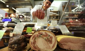 Placing a price label into a joint of ham at an M&S food hall