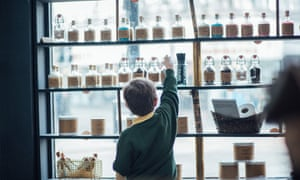 Young boy reaches up to touch a glass jar on a shelf at Grimm & Co Apothecary of Magic, Rotherham, South Yorkshire. UK.