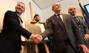 Axel Rütger, director of the Van Gogh Museum in Amsterdam (left), and Naples prosecutor Giovanni Colangelo shake hands in front of the recovered  Van Gogh painting Congregation Leaving the Reformed Church in Nuenen.