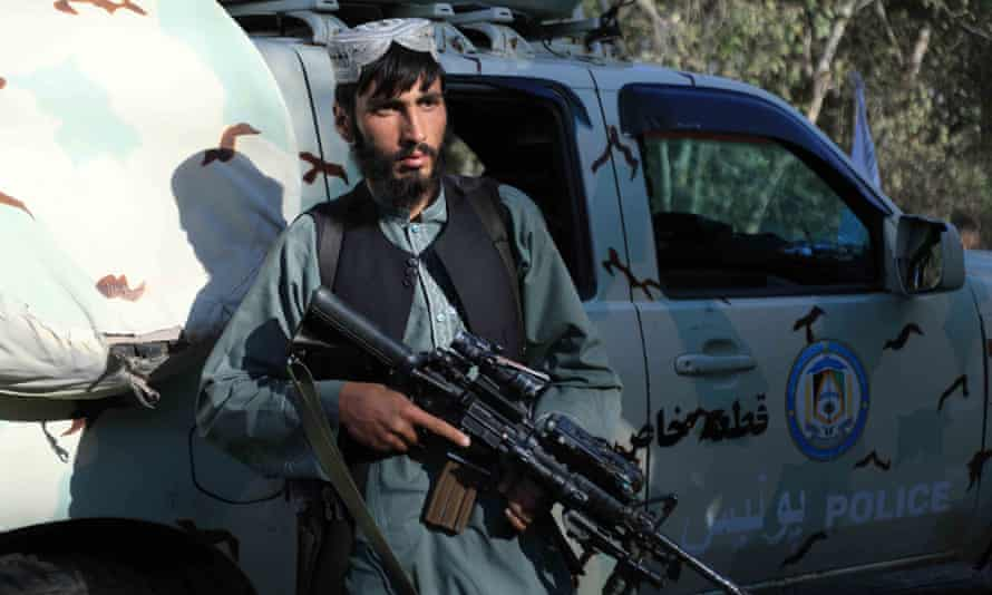 A Taliban fighter with a captured Afghan police vehicle in Herat, Afghanistan's third largest city