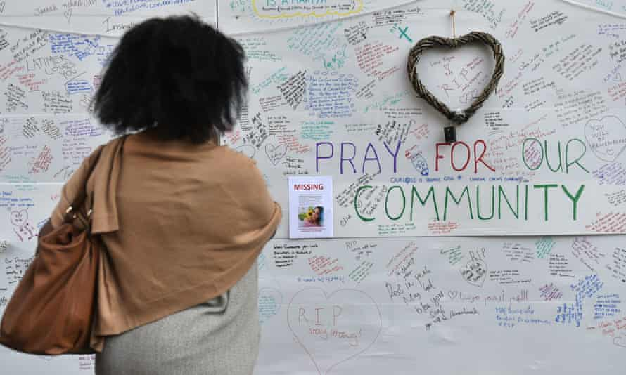 A woman reads a wall of tributes close to Grenfell Tower.