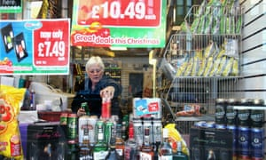 A woman stacks lager in an off licence in Govan, Glasgow, Scotland.
