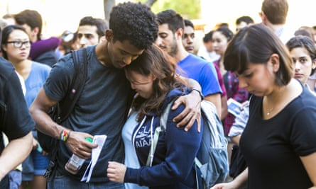 Students hug during a vigil to remember William S Klug in Los Angeles Friday.