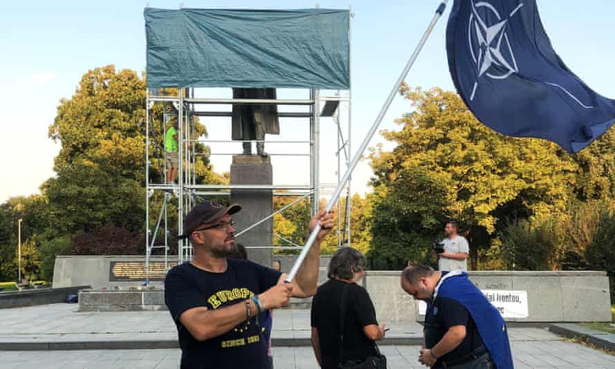 Petr Laznovsky waves a large Nato flag as the cover is reinstalled over Konev's statue.