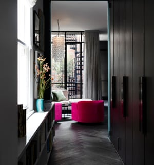 A bank of dark-painted cupboard doors – hiding a laundry room, storage cupboard and toilet – form a corridor connecting the front of the house with the rear