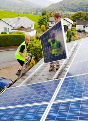 Technicians fitting solar photo voltaic panels to my house roof in Ambleside, Cumbria
