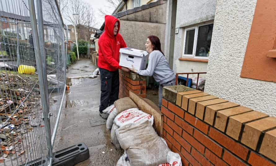 Joanne Mardon receives a food bank delivery outside her flood-affected home in the Rhydyfelin area of Pontypridd