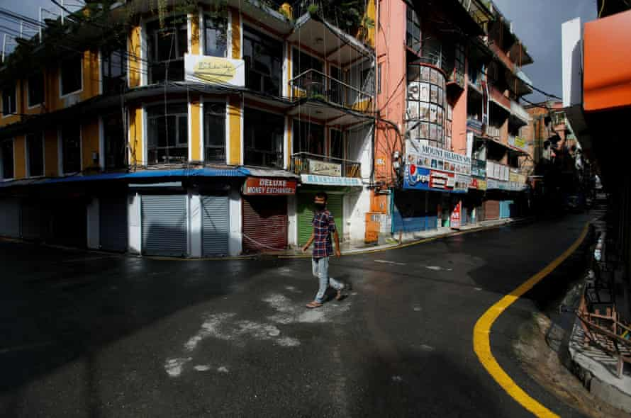 A man walks along empty streets in Thamel, Kathmandu. Once a major tourist hub, the area is deserted and shops are closed after the government imposed restrictions on travel and gatherings to prevent the spread of Covid.