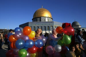 A Palestinian woman holds balloons as Muslims gather for the morning Eid al-Fitr prayer near the Dome of Rock at the al-Aqsa mosque in Jerusalem