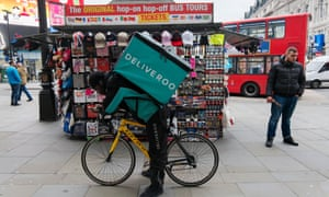 A Deliveroo courier bag cycles through Piccadilly Circus.