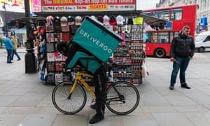 Man with a Deliveroo takeaway courier bag on his back, standing astride his bike in Piccadilly Circus, London, England, UK<br>F7J3XP Black man with a Deliveroo takeaway courier bag on his back, standing astride his bike in Piccadilly Circus, London, England, UK