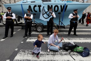 A climate activist sits on the street during a protest outside the Royal Courts of Justice in London, England