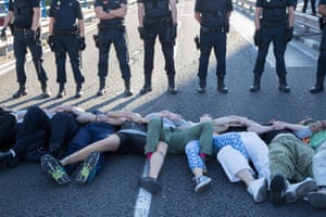 Madrid, Spain. Police watch protesters form a human chain to block roads in the city