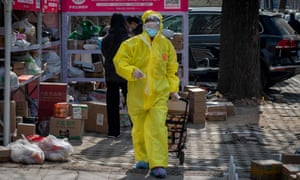 A resident, wearing full protective gear amid fears of the Covid-19 coronavirus, pulls a trolley after collecting packages from a drop-off stall for delivered goods outside a residential compound in Beijing.