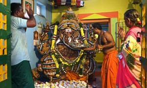 A priest offers prayers in front of an idol of the elephant-headed Hindu god Ganesha made of 1008 coconuts during the Ganesh Chaturthi festival at a temple in Chennai on September 10, 2021.