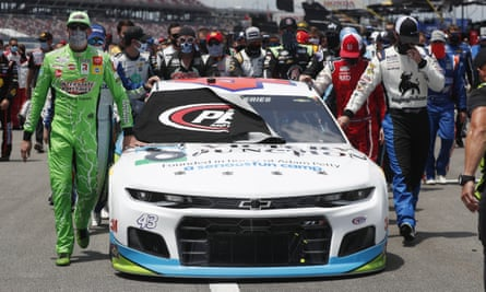 Drivers and crews push Bubba Wallace's car to the front of the field before Monday's race