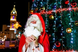 ISRAEL-RELIGION-CHRISTIANITY-ADVENT-HEALTH-VIRUSA man dressed as St Nicholas (Father Christmas or Santa Claus) stands handing out surgical masks next to the lit Christmas tree after the lighting ceremony, in the centre of Israel's Mediterranean coastal city of Tel Aviv on December 6, 2020, as part of efforts against the COVID-19 coronavirus pandemic. (Photo by JACK GUEZ / AFP) (Photo by JACK GUEZ/AFP via Getty Images)