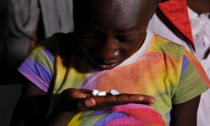 A young girl living with Aids takes her drugs at her home in Ndiwa, western Kenya.