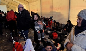 Migrants and refugees keep warm in a large tent as they wait to cross the Greek/Macedonian border, near Idomeni.