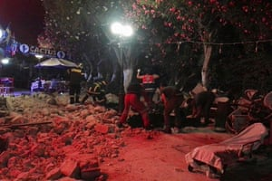 Firefighters remove debris outside a cafe in Kos