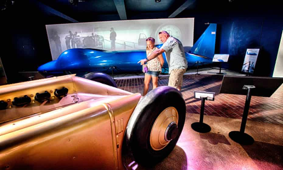 A father and daughter look at land-record-speed breaking cars at the National Motor Museum, Beaulieu, Hampshire, UK>