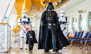 A young cruise passenger joins Darth Vader on deck for Disney's Star Wars at sea.