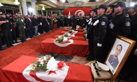 Tunisian police and mourners gather around the coffins of the presidential guards killed in the suicide bombing.