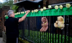 A man places roses on a railing in memory of the victims of the fire.
