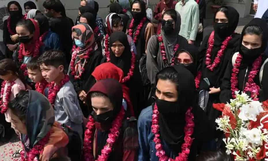 Members of the football team and their families are greeted in Pakistan after fleeing Afghanistan