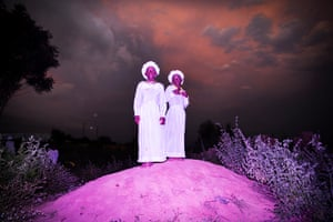 Sisters dressed in white for a ceremony at the Celestial church on a rainy season afternoon