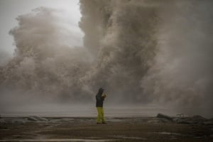 A woman photographs the Mediterranean as waves hit the breakwater during a storm in Barcelona.