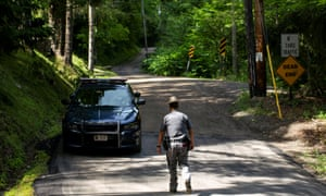 A New York State Trooper stands guard outside the home where attorney Roy Den Hollander was found dead in Catskills, New York Monday.