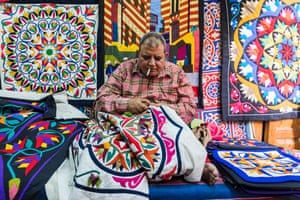 An artisan stitching a new design. For centuries Khayamiya artisans produced tents, cloths and saddles for those embarking on hajj, the pilgrimage to Mecca. The Sultan, sitting nearby on the ancient Fatimid gate, Bab Zuwaila, would watch the caravan depart in procession.