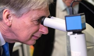 Britain's Finance Secretary Philip Hammond uses a microscope to examine protein crystals during his visit to The Francis Crick Institute in London last week.