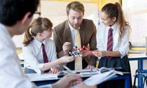 Teacher guiding high school students assembling molecule model in science class