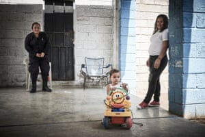 'La Chola' watches her daughter play as a prison guard looks on
