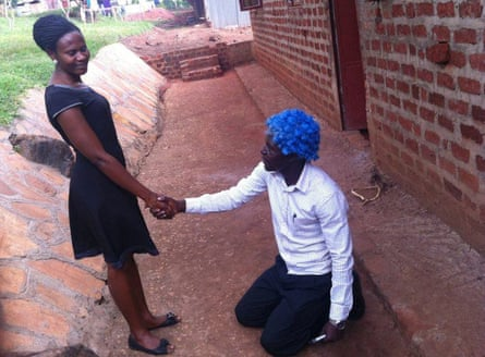 Sam kneels to a female colleague, wearing his blue wig