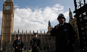 Armed British police officers outside the vehicle entrance to the Houses of Parliament