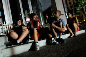 A group of young people sit on the roadside in San Juan