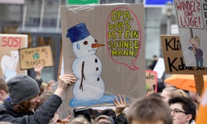 "A student holds a placard reading ""Grandpa, what is a snowman?"""