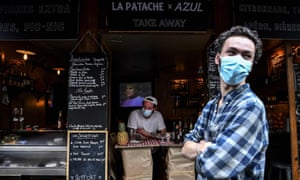 A bartender waits for customers behind a makeshift counter lining the sidewalk in Paris on the 54th day of a lockdown in France. (Photo by Christophe ARCHAMBAULT / AFP) (Photo by CHRISTOPHE ARCHAMBAULT/AFP via Getty Images)